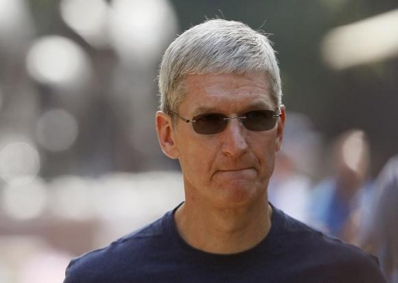 Apple Inc. CEO Cook walks down a sidewalk during the Allen and Co. media conference in Sun Valley